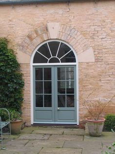 External glazed & panelled French Doors with arched fanlight.
