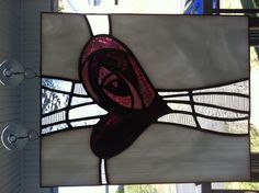 A stained glass piece made as a gift. The heart is done with shades do pink and purple. The cross is done with various clear textured glass.