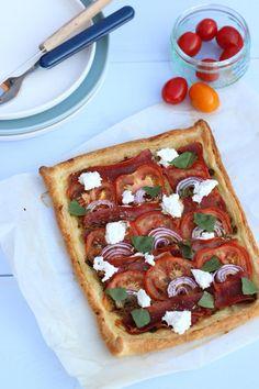 Plaattaart - Lekker en Simpel - Ingredienten: bladerdeeg, pesto, tomaat, parmaham, rode ui, geitenkaas, basilicum