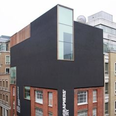 """Architecture: The Photographers' Gallery by O'Donnell + Tuomey: """"..[the architects have]extended a red brick warehouse in central London..Black-rendered walls overhang the original Victorian brickwork to cover the new fourth and fifth floors, which both contain galleries and are lit by a two-storey-high, north-facing window in one corner..Part of the facade is cut away and glazed to reveal the cafe and bar at ground level, and a digital wall in the reception area will present a changing…"""