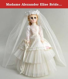 """Madame Alexander Elise Bride Doll - 1685. MADAME ALEXANDER BLONDE BRIDAL DOLL Madame Alexander Elise #1685 Bride based on Elise 17"""" doll wearing a beautiful lace & tulle dress. She's holding a bouquet with white & blue flower in one hand the other has original wrist tag. She's wearing original seamed hose, satin underwear & blue garter w/pink flower, She is in her bridal slippers i. Measures 17"""" high. Comes with mint original box, see images."""
