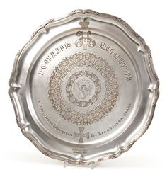 A FINE AND IMPORTANT FABERGE SILVER PRESENTATION SALVER, MOSCOW CIRCA 1900.  The imposing platter with scalloped rim and edged with reeded ribbon-tied border. The cavetto engraved with the Imperial Double Headed-Eagle and scrolling foliage on a matt ground. Also engraved with the Imperial cipher of Nicholas II and Cyrillic inscription: 'To His Imperial Majesty Nicholas II from Kirasirsky His Majesty Guard Regiment - Petergoff June 20 1909', above the Regimental Badge.