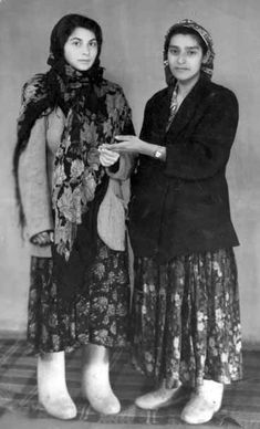 Two Romani women standing side by side, full length.