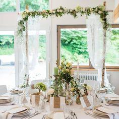 Ein Blütenbogen am Brauttisch ist auch eine tolle Deko für Eure Hochzeit.