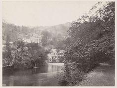 Anonymous | Panoramisch uitzicht op huizen tegen een heuvelrug aan een water in Matlock, op de voorgrond een overgroeid pad, Anonymous, 1878 - 1890 | Onderdeel van Reisalbum Europese steden, vermoedelijk Zweeds.