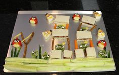 Angry Birds Fun Food For Kids Lunch - PBJ Sandwich Towers; Pretzel & Carrot Posts; Pretzel & String Cheese Slingshot; Cucumber Grass; All birds have candy eyes (bought at Hobby Lobby); Babybel Red Birds (Cheddar Beak & Olive Eyebrows, Olive Tail Feathers); Laughing Cow Yellow Birds (American Cheese Topper, Carrot Stick Eyebrows, Cheddar Beak, Olive Hair); Kiwi Pigs (Cucumber Nose Round with Peppercorn Nostrils, American Cheese Crown).
