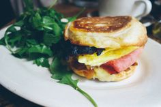 Egg sandwich with ham, gruyere, caramelised onions & maple bacon on an English muffin