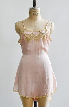 "Name:A Kiss For Morning Step-In $128.00 Vintage 1920s pale rose pink step in. Vintage late 20s step in features pretty cream lace festoon inserts at bodice, lace trim along edges, and lightly flares at the hips. Self tie sash.  measurements - 31"" length - 36"" bust - open waist - best fits small  details - silk crepe de chine - excellent vintage condition"