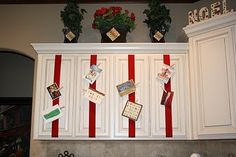 Christmas card holder: ribbon wrapped around cabinet door with clothes pins to attach cards. This would save us from taping cards to the doors and add a little color.