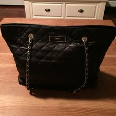 Black quilted tote Gorgeous black quilted tote bag. Inside is black satin. Chain straps. Perfect inside and out only used once. Can fit a lot. In between large and medium size. DKNY Bags Shoulder Bags