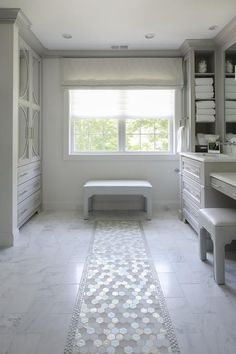 White and gray glass hex tiles lead to a light gray bench placed on white marble staggered floor tiles beneath a window dressed in a light gray roman shade.