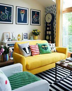 Sofá amarelo e almofadas em diversas cores pra um resultado moderno e hiper colorido. Mais fotos assim no post do Blog Midá. Clica lá!
