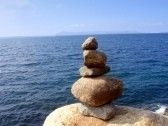 Stone balancing over the blue sea and sky stock photography