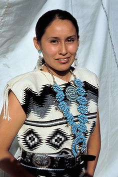 Traditional Navajo woman models a traditional Navajo womans woven wool dress with typical patterns of the Navajo weaver and decorated with a turquoise squash blossom necklace