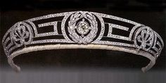 This tiara was wedding gift to then Princess Elizabeth from her mother-in-law Princess Andrew of Greece and Denmark (born Princess Alice of Battenberg). The meander tiara is in the classical Greek 'key pattern' featuring a large brilliant cut diamond in the centre surrounded by a diamond wreath. The tiara also incorporates a central wreath of leaves and scrolls on either side. The Queen has never worn it in public and it was given to Princess Anne around 1972. Princess Anne has frequently…