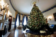 The official White House Christmas tree, the centerpiece of the Blue Room, is on display during the first viewing of the 2011 White House Christmas decorations. Honoring Blue Star families, the 18-foot 6-inch balsam fir tree is decorated with framed military medals and handmade holiday cards created by military children living on installations around the world. The theme, 'Shine, Give, Share,' runs throughout the White House with a 400-pound White House Gingerbread House and 37 Christmas…