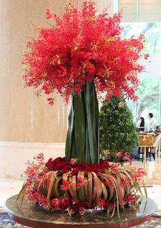 Florist Abby Ho and her team used over 100 celosia and phormium flowers to shape the base, as well as bright crimson gloriosa lilies and aranda orchid blooms to create a fire sparkle effect. Do you like our lobby's Fountain of Glory centrepiece?