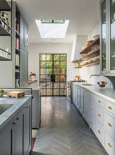 Light-filled kitchen, with warm gray painted cabinets, brass hardware and drawers pulls, open shelving and gray parquet flooring.