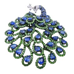 Diamond Sapphire Tsavorite Peacock Pin Brooch. Beautiful Diamond Sapphire Tsavorite Peacock Pin Brooch composed of 22 brilliant-cut diamonds=0.12ct, 1 black diamonds=0.02ct, 34 sapphires=9.93ct and 610 tsavorite=6.25ct; claw-set in 18k white gold; Total weight: 26.50gm. Via 1stdibs.