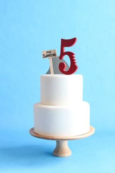"The options are endless with this DIY Shark, No Swimming Cake Topper Kit. Decorate your marine enthusiasts cake with this adorable topper. The kit includes a shark fin, one number with a shark bite (select from 1 through 9) and a shabby No Swimming sign. The fin and number have a stick to insert into the cake to secure the items in place.  This topper is exactly what you need for your aquatic aficionados birthday or any other joy-filled event.  Measurements are:  Number * : 5"" Tall (without…"
