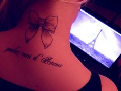 Neck bow tattoo with french quote.
