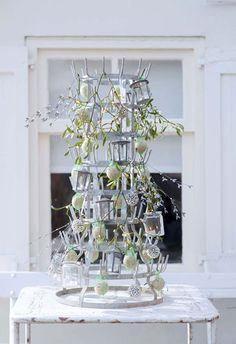 en (oud) flessenrek kun je net zo geweldig aankleden als een kerstboom. Hang vol met minilantaarns, belletjesballen en takjes mistletoe. Een feest om naar te kijken op de buitentafel. Met vetbollen in netjes wordt het ook een feestje voor vogels.
