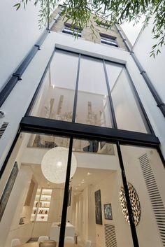 Hier ist der Blick in die massive, doppelte Höhe Küche und Esszimmer Raum, überschwemmt mit Tageslicht durch Fenster volle Höhe. Oben sind die mehr vertraut konstruierten Böden umwickelt Ziegel sichtbar.