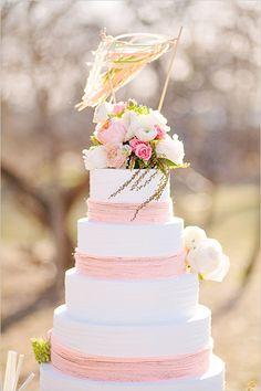 Gâteau de mariage rose et blanc, orné de fleurs