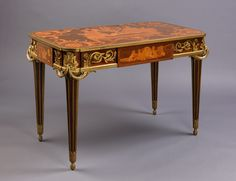 'La Table des Muses', A Very Fine Louis XVI style Gilt-Bronze Mounted Mahogany and Marquetry Centre Table by François Linke After the Model By Jean-Henri Riesener.  French, Circa 1900.