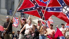 Members of the Ku Klux Klan yell as they fly Confederate flags during a rally at the statehouse in Columbia, South Carolina July 18, 2015. A Ku Klux Klan chapter and an African-American group planned overlapping demonstrations on Saturday outside the South Carolina State House, where state officials removed the Confederate battle flag last week.