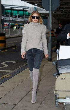 Gigi Hadid wears a gray Iro sweater, distressed Citizens of Humanity jeans, over-the-knee gray suede Stuart Weitzman boots, and sunglasses