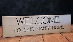 Welcome Hand-Painted Sign, by Our Backyard Studio in Mill Creek, WA. Features black lettering on a white-washed background. Sanded, stained, and antiqued for a weathered look. Back side and edges are stained. Sign is sealed with wax, has a sawtooth hanger attached. Measures approx 21 inches wide, 5.5 inches high, and 3/4 inch thick. Made of pine - knots, nick...