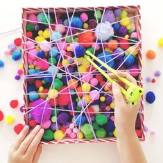 Love this fun fine motor activity created To set it up she simply wrapped wool/yarn around a shoe box lid to create the web effect, and then filled it up with pom-poms. How easy (and cheap) is that? We think this activity would Sensory Bins, Sensory Activities, Infant Activities, Preschool Activities, Colour Activities Eyfs, Motor Skills Activities, Gross Motor Skills, Fine Motor Activity, Fine Motor Activities For Kids