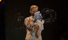 Tilda Swinton, wearing a plain white robe, the kind once worn by the models in the couture salon of Yves Saint Laurent, walks on the runway, holding — but never actually wearing — articles of clothing from the historic archives of the Galliera, the Paris museum of fashion.