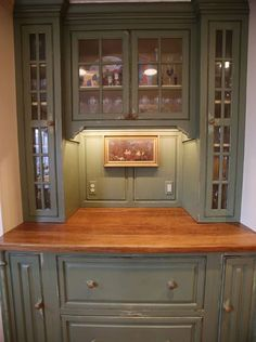 At one end, a moss green built-in cupboard looks like