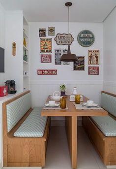 Decoração de apartamento com cores neutras, na sala de jantar mesa de madeira e bancos estofados.