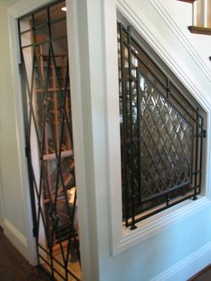Wrought iron wine room gate brings an antique feel to an otherwise modern space-Great for small space under the stairs [by The Looking Glass].