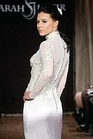"""Model walks runway in a Dominique Bridal dress - long sleeve sheer illusion beaded gown, by Sarah Jassir, for the Sarah Jassir Spring 2013 """"La Reve: The Dream"""" collection, during Bridal Fashion Week New York."""