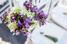 purple and cream arrangement on aisle chairs