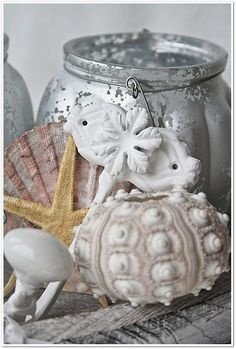 Seashell decor mixing mercury glass with shells, starfish and other bits and bobs. Use a variety on tables.