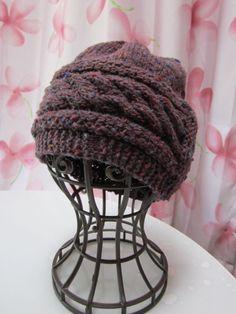 縄編み2本のベルトのようなデザインが特徴の手編み帽子です。木ボタンがついたフラップがアクセントです。こちらの毛糸は、紫地に、オレンジ・グリーンなどのゴマが入っ...|ハンドメイド、手作り、手仕事品の通販・販売・購入ならCreema。