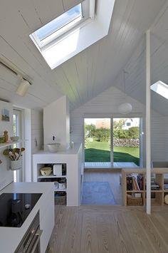 Los techos con sus ventanas y el verde exterior, iluminan el ambiente, en esta casa danesa de veraneo ...