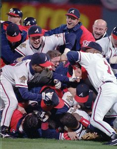 In this Oct. 28, 1995, file photo, the Atlanta Braves celebrate their 1995 World Series win against the Cleveland Indiants at Atlanta Fulton County Stadium in Atlanta. After a one-year delay caused by the 7 and a half-month players' strike, the expanded playoffs began in 1995, when teams played a 144-game schedule because of the walkout. The top teams met that October, with Atlanta defeating Cleveland in six games. (AP Photo/Andrew Innerarity, File)