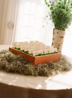 make box of wood or cardboard, fill with styrofoam add moss and make copper card holders, insert copper holders into moss to hold cards.  add moss under box and a vaseof flowers. Great display for outoor market and to attract people over with clever display