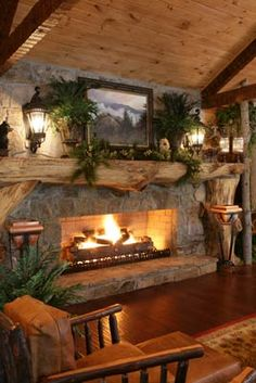 LOVE a split-log mantel on a stone fireplace in a rustic cabin ... looks nice with carriage lights and framed landscape, hardwood flooring with area rug, leather and wood furniture, exposed beams and vaulted ceiling, green plants (ferns are ideal) - very nicely put together room!