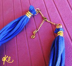 detalle del cierre del mismo alambre, cierre con cadena dorada y detalle colgante, color violeta y dorado....
