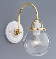 Rejuvenation Bath: Our Mist Arched Sconce combines porcelain canopy and sockets with brass.