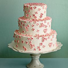 Pink Cherry Blossoms Cake | Take your favorite flower and run with it. Small pink blossoms spill down the sides of this tiered buttercream-frosted cake.