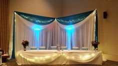 White Pipe & Drape with White & Turquoise Swags, Uplights and White Table Drape at Bunker Hills Activity Center by Deckci Decor