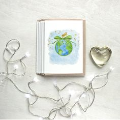 Set of holiday greeting cards featuring a watercolor painting by Kathleen Maunder. A simple message of peace for Christmas and the new year.